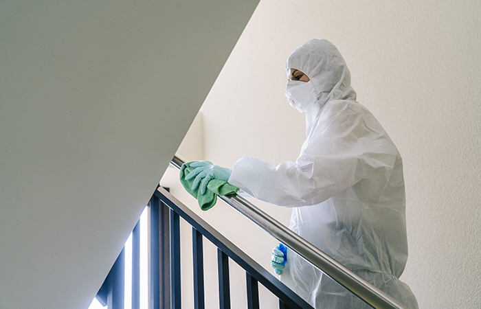 A person wearing a mask, gloves and a safety suit cleans and disinfects a doorway of a community flat in the face of a virus pandemic, protected safety equipment so as not to be infected