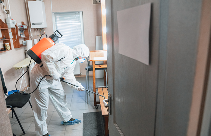 Coronavirus Pandemic. A disinfector in a protective suit and mask sprays disinfectants in house or office. Protection against COVID-19 disease. Prevention of spreding pneumonia virus with surfaces.